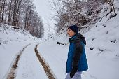 stock photo of snowy-road  - Teenage boy walking on a snowy country road through the forest - JPG