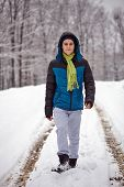 image of trough  - Full length portrait of teenage boy walking on a snowy country road trough the forest - JPG