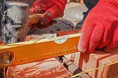 image of bricklayer  - Bricklayer with brick at a construction site - JPG