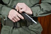 picture of black-cock  - The soldier shutter cocking a pistol gun - JPG
