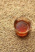 stock photo of malt  - Tumbler glass with whiskey standing on barley malt grains - JPG