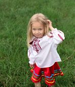 foto of national costume  - little blonde girl in ukrainian national costume are playing with her hair - JPG