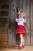 picture of national costume  - Little ukrainian girl in national traditional costume trying to open old wooden door - JPG