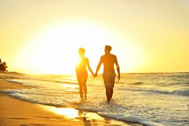 pic of couple  - Honeymoon romantic couple in love holding hands walking on beautiful sunset at beach in waterfront - JPG