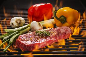 stock photo of braai  - A New York Steak on a hot flaming grill with red and yellow peppers - JPG