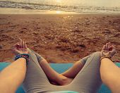 picture of pov  - Young woman meditating in pose of lotus on beach at sunset in summer point of view - JPG