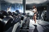 foto of bum  - Nice sexy woman doing workout with dumbbells in gym - JPG