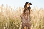 stock photo of tallgrass  - Beautiful young model walking through tallgrass meadow - JPG