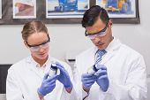stock photo of concentration  - Concentrated scientists looking at medication in laboratory - JPG