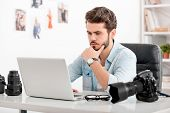 picture of concentration man  - Concentrated young man holding hand on chin and looking at laptop while sitting at his working place  - JPG