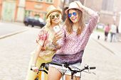 image of tandem bicycle  - A picture of two girl friends riding a tandem bicycle and taking selfie in the city - JPG