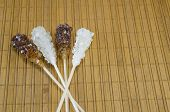 picture of sugar  - Two sugar sticks containg white and brown sugar against a wooden table - JPG