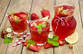 picture of cold drink  - Cold strawberry drink with fresh strawberries and lemon on wooden background - JPG