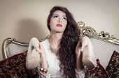 stock photo of bolivar  - Pretty model girl sitting on victorian sofa posing for camera holding both shoes up - JPG