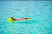 stock photo of legs air  - Happy Woman relaxing on inflatable air mattress at turquoise water - JPG