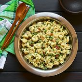 stock photo of dark side  - Tortellini salad with green peas fried bacon and parsley in big salad bowl with small rustic bowls wooden spoon and fork on the side photographed overhead on dark wood with natural light - JPG
