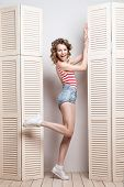 foto of jalousie  - Young beautiful woman wearing shorts and  stripy top posing in front of a jalousie - JPG