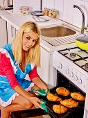 image of bap  - Young woman bake cookies in stove in kitchen - JPG