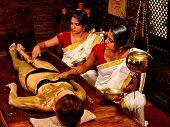 stock photo of panchakarma  - Young woman having green clay body spa massage - JPG