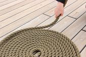 picture of roping  - Old nautical thick rope wrapped in spiral lying on weathered deck of yacht circle of thick rope with hand of woman - JPG