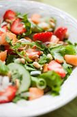 stock photo of cantaloupe  - Summer salad with strawberries and cantaloupe - JPG