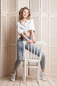 stock photo of jalousie  - Beautiful woman wearing pants and shirt sitting on a chair in front of a jalousie - JPG