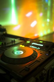 picture of social housing  - DJ console cd mp4 deejay mixing desk Ibiza house music party in nightclub with colored disco lights.