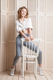 foto of jalousie  - Beautiful woman wearing pants and shirt sitting on a chair in front of a jalousie - JPG