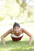Постер, плакат: Молодая женщина упражнения в парке