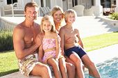 stock photo of swimming pool family  - Family Outside Relaxing By Swimming Pool - JPG