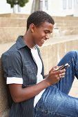stock photo of teenage boys  - Male Teenage Student Sitting Outside On College Steps Using Mobile Phone - JPG