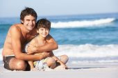 Father And Son Wearing Swimwear Sitting On Sandy Beach
