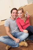 Young couple sit on the floor around boxes holding key in hand