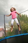 foto of bounce house  - Small cute child jumping on trampoline  - JPG