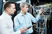 two network support engineers administrating in server room poster