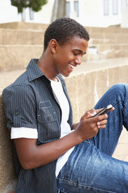picture of teenage boys  - Male Teenage Student Sitting Outside On College Steps Using Mobile Phone - JPG