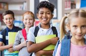 Portrait of a happy multiethnic children holding books and wearing backpack at primary school. Schoo poster