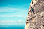 Rock Climber On A Rock. Woman In Helmet Climbs The Rock On The Background Of A Beautiful Sky With Cl poster