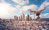 multicopter drone flying over the cityscape of Frankfurt am Main, Germany, financial capital of the  poster