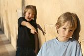 stock photo of bullying  - childhood problems boys bullying school bully and his sad lonely victim - JPG