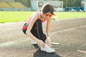 Beautiful Teenage Girl Running In Stadium, Tying Laces Of Running Shoes Before Training poster