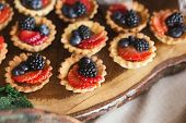 Closeup Of Berry Mini Tarts On Wooden Board. Small Tartalettes For Party Dessert Stand. Candy Bar An poster