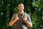 Handsome Bearded Male Backpacker With Backpack On His Shoulders. Attractive Tourist With Backpack. T poster
