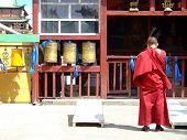 foto of ulaanbaatar  - A Buddhist monk wearing red bowing head in prayer at Gandantegchinlen Khiid in Ulaanbaatar - JPG