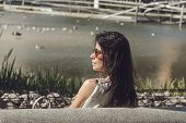 Portrait Of Young Woman In The Park. Woman With Sunglasses Sitting On The Park Bench. Young Woman In poster