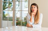 Young beautiful woman at home thinking and looking up expressing doubt and wonder poster