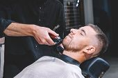 Young Male Barber Shaves The Clients Beard With A Electric Trimmer. Young Bearded Man Getting Haircu poster