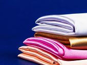 Rolls Of Silk Of Different Colors Folded Stack. Colorful Fabric Silk Stack Background. poster