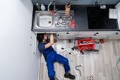 High Angle View Of Male Plumber In Overall Fixing Sink Pipe poster