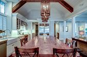 Large luxury kitchen with wood table and high end appliances. poster